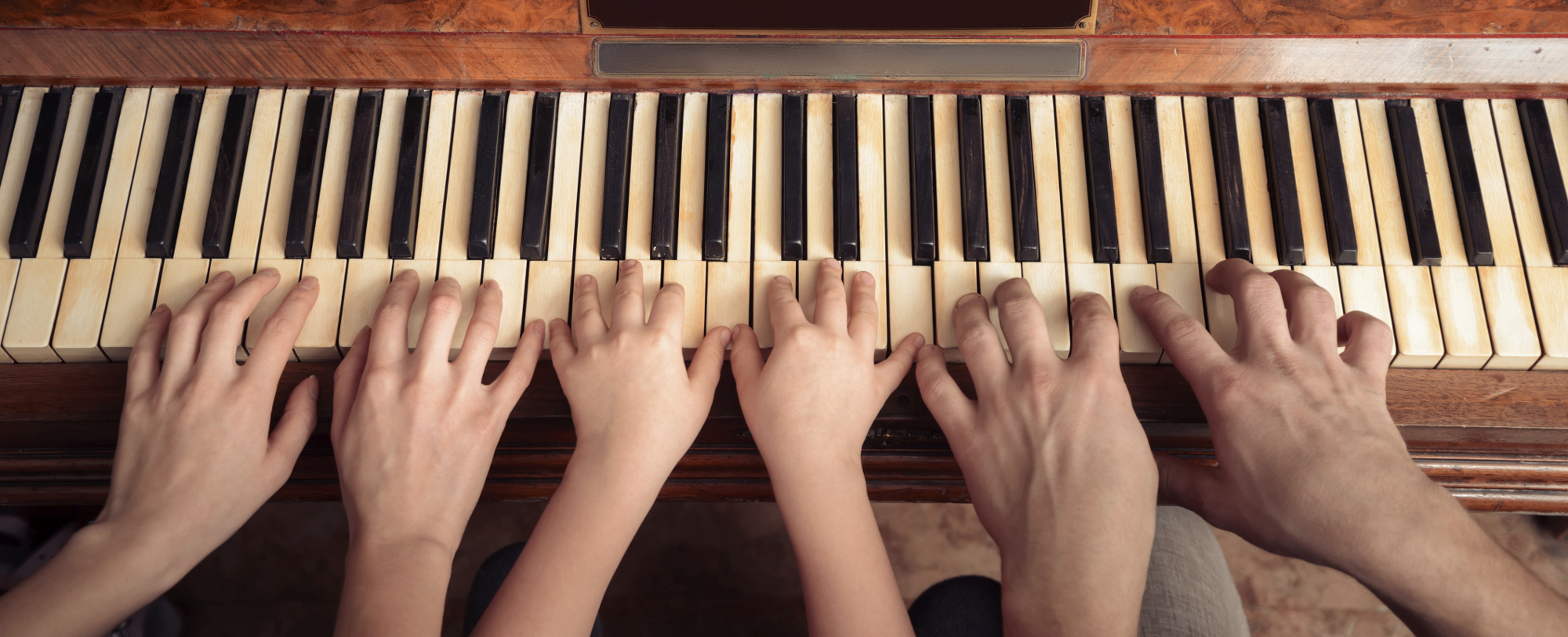 Hands of different ages playing a piano